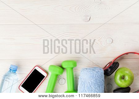Fitness and diet concept background. Dumbbells, water bottle, smartphone, headphones and apple. Top view with copy space
