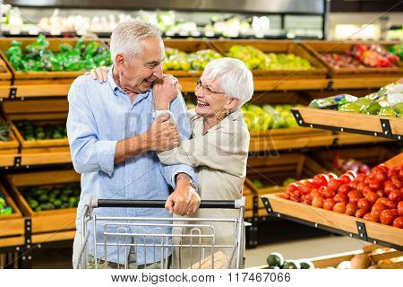 Happy senior couple with cart at the grocery shop