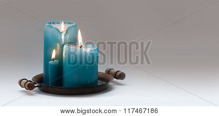 Romantic still life with turquoise different size candles on vintage metal plate. natural flame and