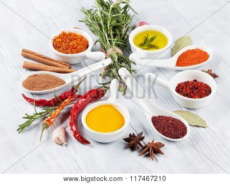 Herbs, condiments and spices on wooden background