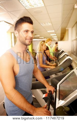Young man training in running machine in gym.