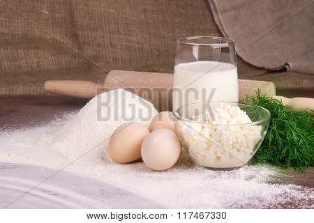 Glass Cup With Milk, A Glass Bowl With Cottage Cheese, Eggs, Flour, Dill, Moldovan Palanitsa On A Wo
