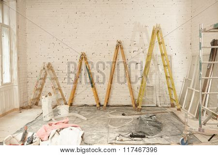 Renovation site with ladders of different height.