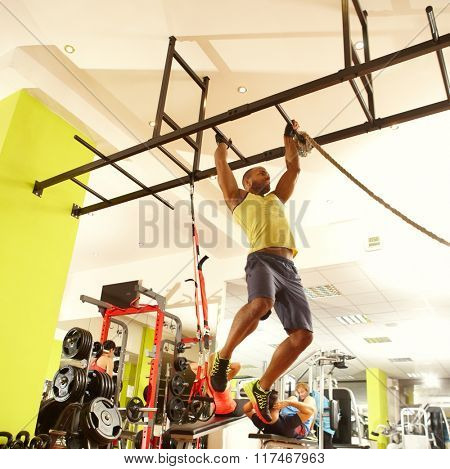 Sporty ethnic man training in fitness club, hanging on.