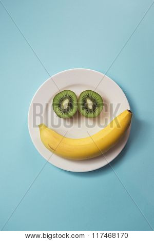 Smiling face made from banana and kiwis