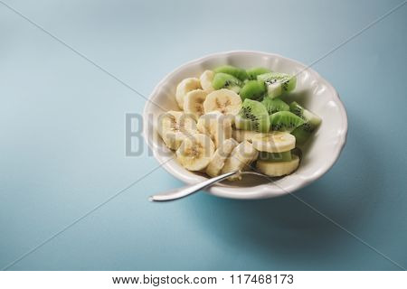 Fruit salad with kiwi and banana slices in bowl