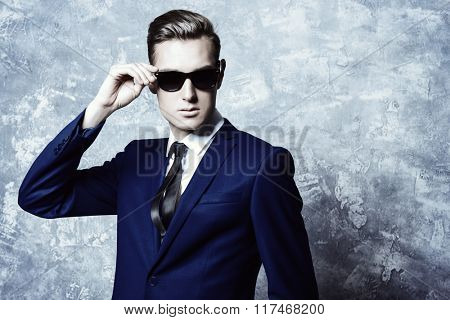 Close-up portrait of a handsome man in elegant classic suit and sunglasses. Men's beauty, fashion.