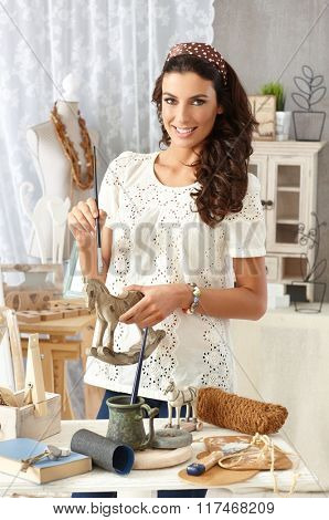 Young woman painting wooden horse, enjoying hobby at retro home.