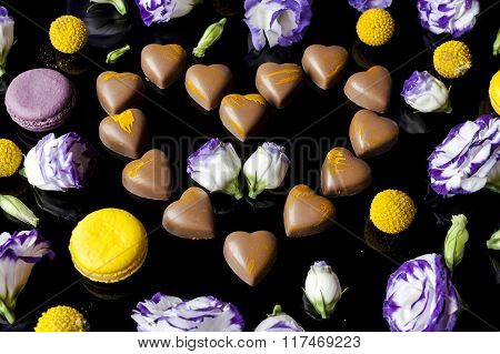 Milk chocolates heart surrounded with flowers from side on black