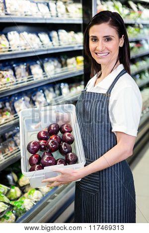 Pretty brunette holding box of vegetable in supermarket