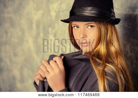 Beautiful teen girl in autumn clothes posing by a grunge wall. Seasonal fashion. Youth style.