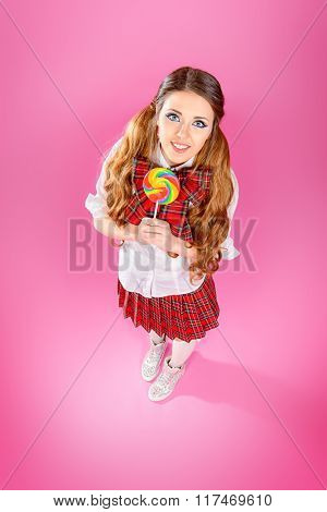 Full length portrait of a pretty smiling teen girl in school uniform posing over pink background. Anime style.
