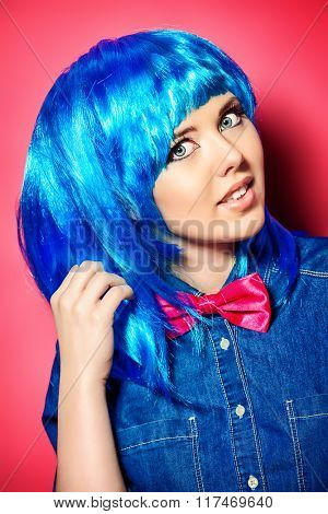 Beautiful girl wearing bright blue wig and jeans clothes posing over pink background. Beauty, fashion.