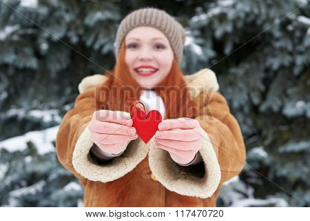 Young woman give red heart toy. Winter season. Outdoor portrait in park. Snowy weather. Valentine concept. Focus on hands. Shallof dof.