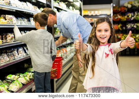 Smiling daughter with thumps up in grocery store