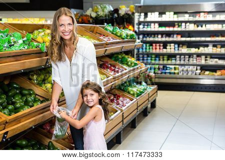 Mother and daughter doing shopping in grocery store