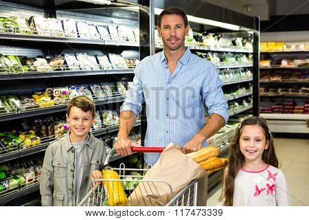 Smiling family doing shopping in grocery store