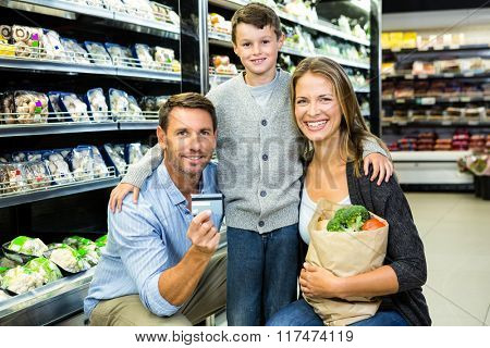 Portrait of family showing credit card in grocery store