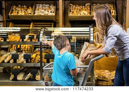 Mother and son looking at bread in grocery store