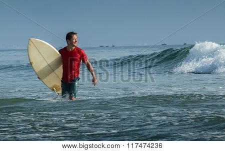 Happy surfer with short board walking from the ocean