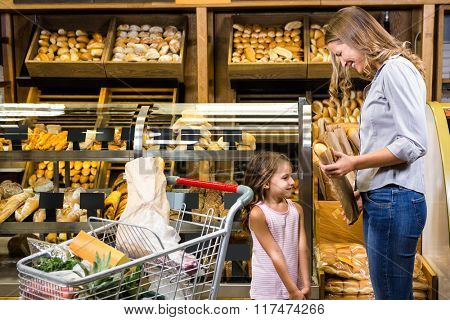 Mother and daughter taking bread in grocery store