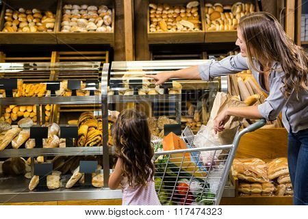 Mother and daughter looking at bread in grocery store