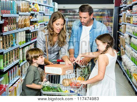 Happy family doing shopping in grocery store