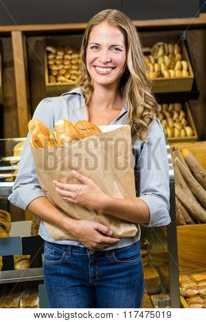 Portrait of woman holding paper bag in grocery store