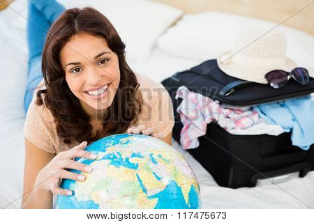Smiling woman lying on bed while holding a globe at home