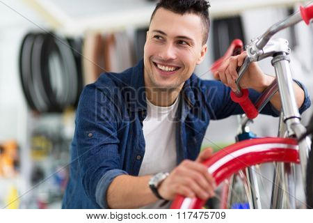 Technician fixing bicycle in repair shop