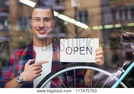 Bike shop owner holding open sign