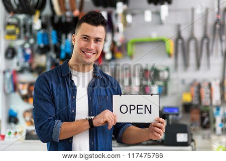 Bike shop owner holding open sign