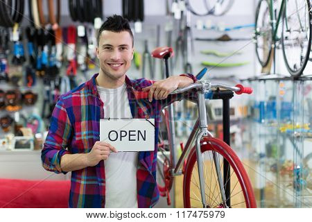 Man holding open sign in bike shop