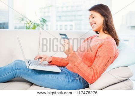 Smiling woman with a credit card and a laptop on a sofa at home