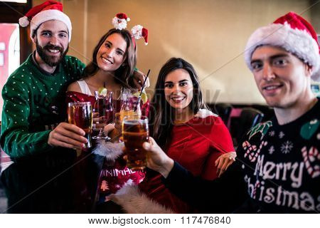 Festive friends drinking beer and cocktail in bar