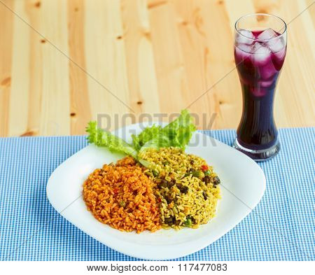 Delicious Dish Made Of Two Kinds Of Rice On A White Plate And A Glass Of Juice With Ice