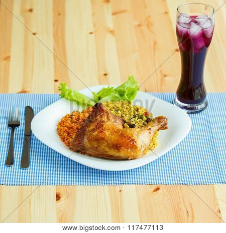 Dishes From Chicken Thigh With Rice And Lettuce And A Glass Of Juice With Ice