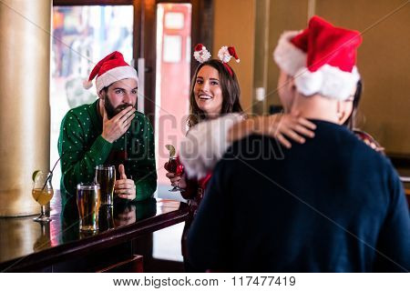 Festive friends in a bar together
