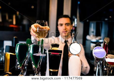 Barman giving a drink to customer in a bar