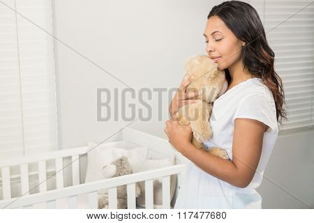 Smiling brunette holding plush in bedroom