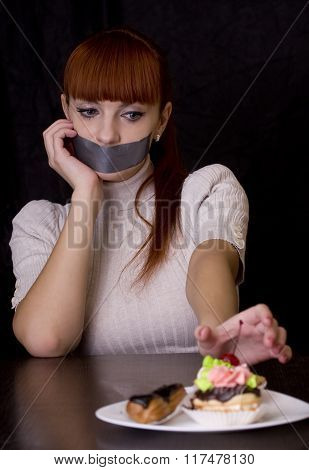 The Girl, Whose Mouth Sealed With Tape Sad Looking At Plate With Cakes