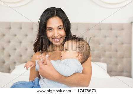 Happy brunette holding her baby in bedroom