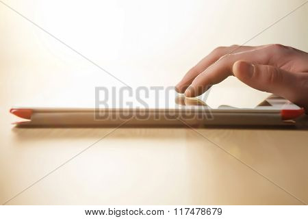 The tablet with the hand on wooden table