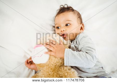 Cute baby holding plush on bed
