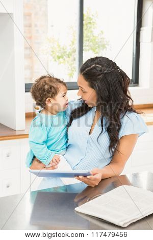Smiling brunette holding her baby and using tablet in the kitchen