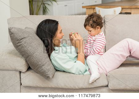 Smiling brunette playing with her baby on the sofa