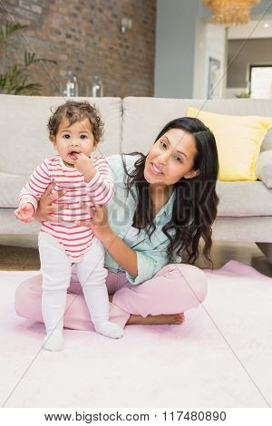 Happy mother with her baby daughter on the carpet in living room