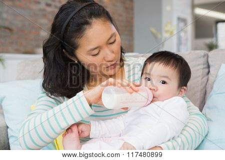 Mother giving milk in bottle to her daughter on the sofa