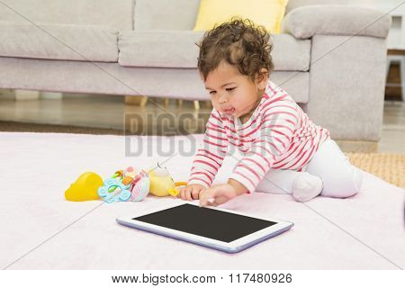 Cute baby on the carpet with tablet at home