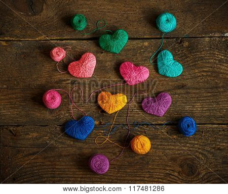 Multicolored Hearts With A Balls Of Thread On Old Shabby Wooden Background